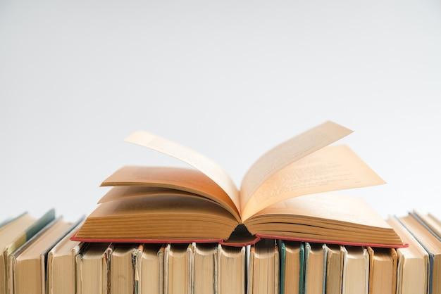 Libro aperto su sfondo bianco, libri con copertina rigida sulla tavola di legno.