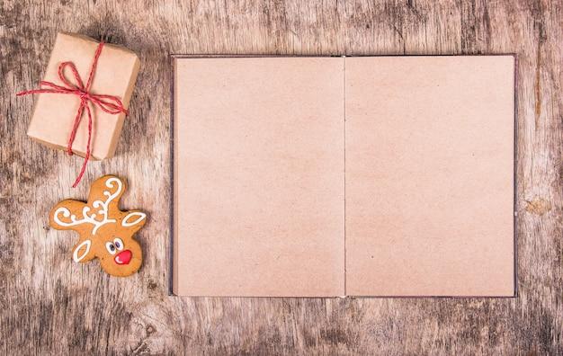 Libro aperto con pagine vuote, pan di zenzero e una confezione regalo