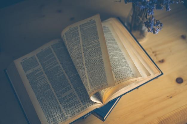 Apra il libro sullo scrittorio di legno nella stanza delle biblioteche con il fuoco vago per il fondo di istruzione