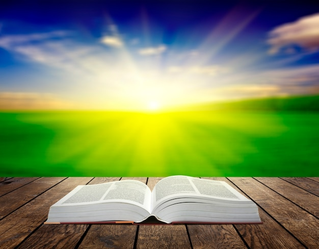 Libro aperto su tavola di legno sopra i raggi del tramonto. superficie del concetto di educazione