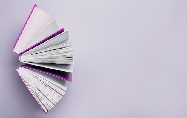 Libri aperti su uno spazio viola