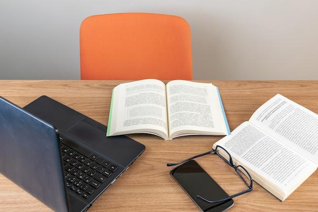 Apri libri sul tavolo accanto a notebook, smartphone e occhiali.