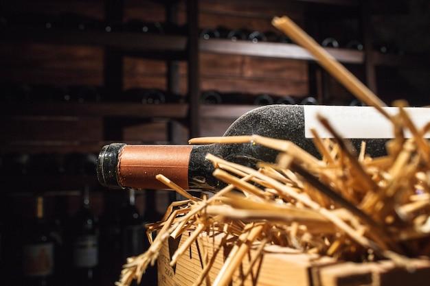 Aprire la bottiglia di vino coperto di polvere si trova sul fieno