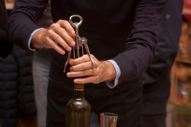 Aprire una bottiglia di vino con un cavatappi a una festa.
