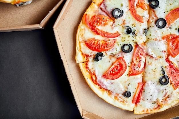 Scatola aperta con pizza a fette italiana gustosa calda su sfondo nero, fast food delizioso, concetto di consegna, vista dall'alto, spazio copia, piatto laici.