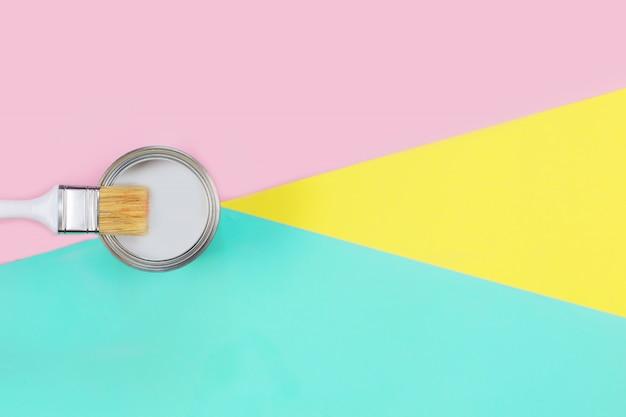 Aprire la lattina con vernice bianca e pennello sul muro color pastello.