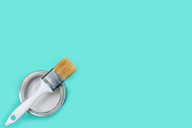 Aprire il barattolo con vernice bianca e pennello su sfondo azzurro,