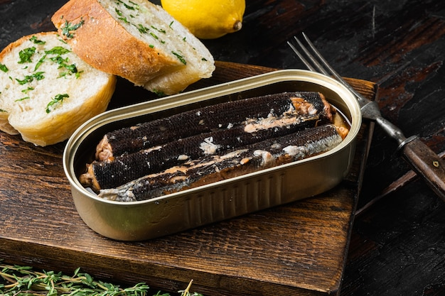 Aprire il set di pesce in scatola, su un vecchio sfondo di tavolo in legno scuro