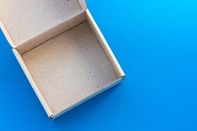 Scatola di cartone aperta su sfondo blu. pacco ecologico, imballaggio. vista dall'alto, piatto.