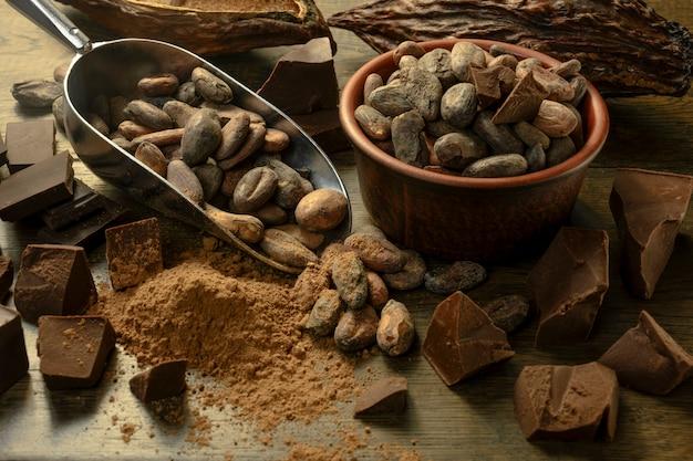 La frutta aperta del cacao si trova su un tavolo di legno con fave di cacao