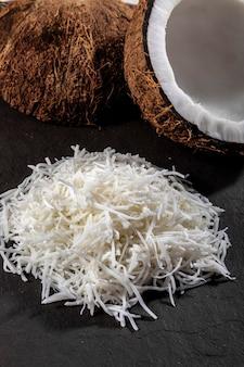 Aprire il cocco al centro sopra la pietra con scaglie di cocco e cocco grattugiato.