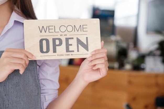 Aprire il testo del negozio di caffè caffè a bordo appeso alla porta di vetro nella moderna caffetteria caffetteria, riapertura bar ristorante, negozio al dettaglio, concetto di proprietario di piccola impresa
