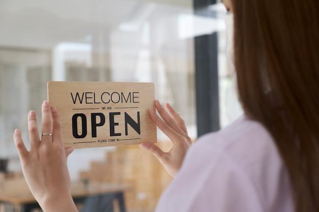 Aprire il testo del negozio di caffè a bordo appeso alla porta di vetro nella moderna caffetteria