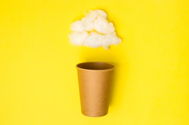 Apra la tazza di carta del mestiere con la nuvola dell'ovatta su un fondo giallo. disteso. creativo concetto di cibo minimo.