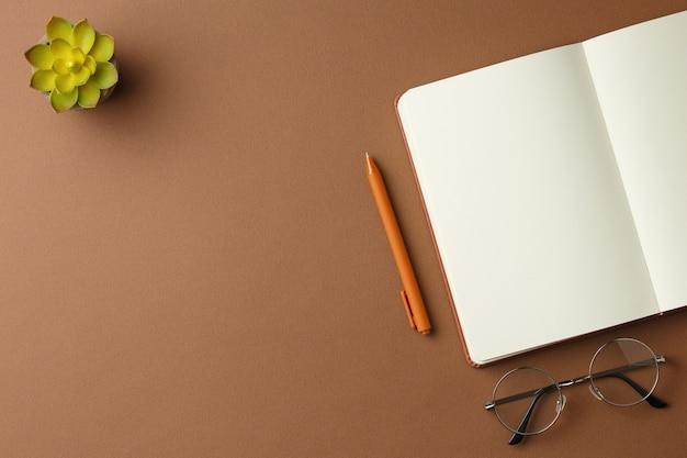 Diario aperto con bicchieri da penna e una pianta in vaso