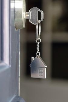 Apri la porta di una nuova casa con la chiave e il portachiavi a forma di casa. mutui, investimenti, immobili, proprietà e nuove attività di concetto di casa