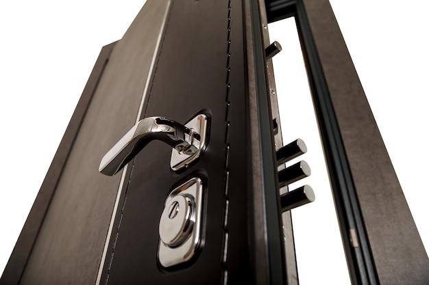 Una porta aperta con serrature. porta moderna con maniglie e serrature in metallo cromato. elementi interni. sicurezza domestica. primo piano della serratura della porta blindata. posto per la tua creatività con spazio per testo o logo