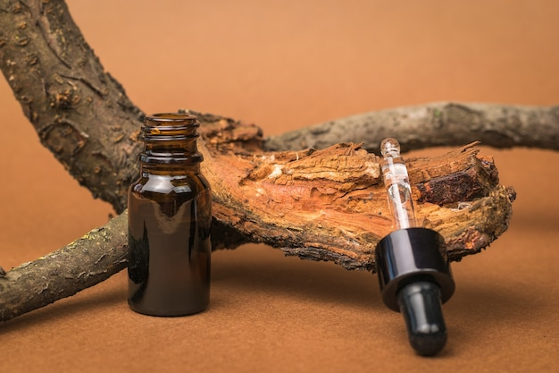 Un flacone contagocce aperto e un vecchio albero su uno sfondo marrone. cosmetici e medicinali a base di minerali naturali.