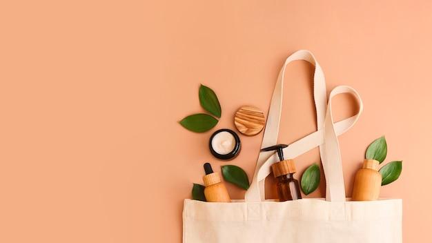 Sacchetto riutilizzabile in cotone ecologico aperto con i contenitori cosmetici colori pastello