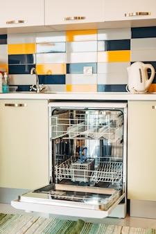 Una lavastoviglie vuota aperta in una cucina bianca decorata con piastrelle gialle e bianche blu