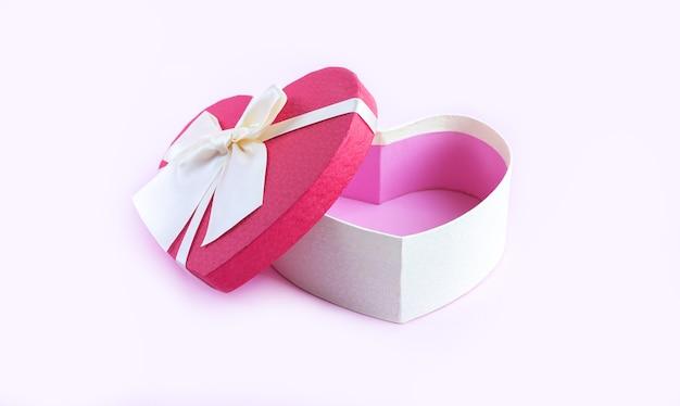 Apri scatola regalo vuota a forma di cuore con fiocco a nastro sul tavolo rosa