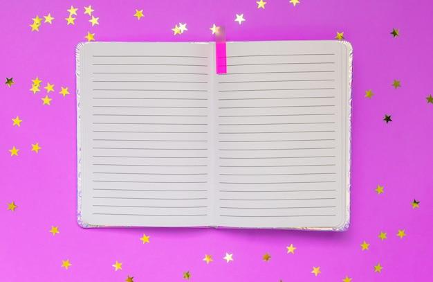 Apra il taccuino vuoto su una parete rosa con i coriandoli delle stelle. vista dall'alto. spazio per testo o design