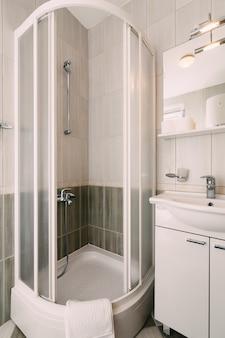 Aprire il box doccia vuoto e il lavabo in bagno con piastrelle bianche