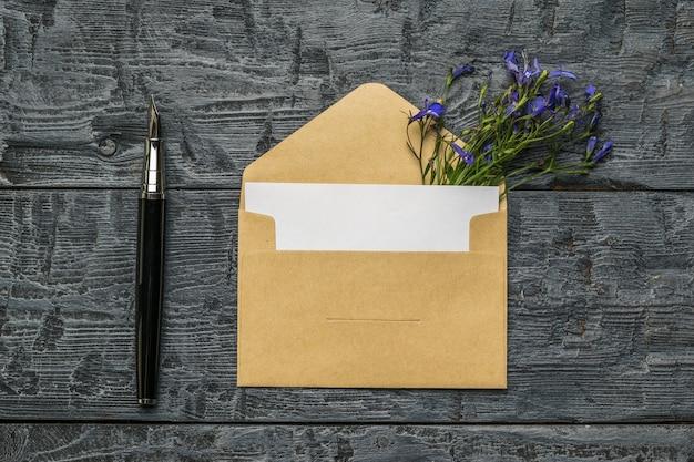 Una busta aperta con un foglio di carta bianco, una penna stilografica e fiori su uno sfondo di legno. disposizione piatta.