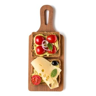 Crostini o crostini a sandwich con la faccia aperta su un tagliere di legno isolato su priorità bassa bianca