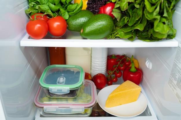 Frigorifero aperto pieno di frutta, verdura e bevande