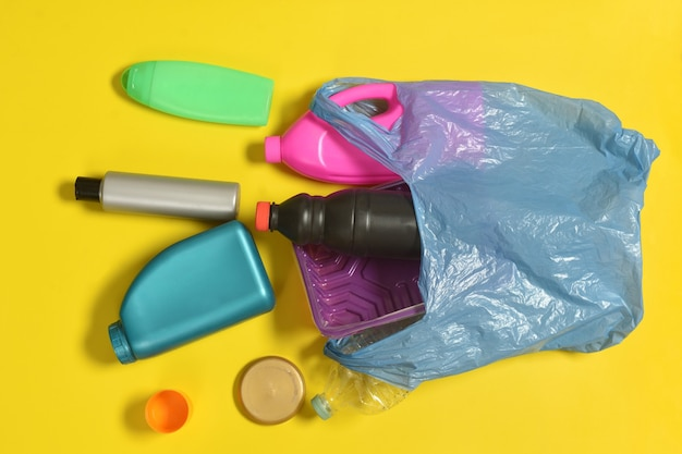 Aprire il sacchetto della spazzatura con bottiglie di plastica sparse