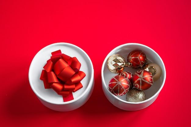 Scatola regalo aperta con palle di natale su uno sfondo rosso.