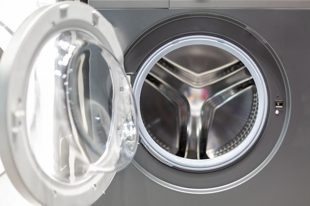 Aprire lo sportello di vetro di un tamburo della macchina a strisce di acciaio grigio di una vista frontale della lavatrice da vicino