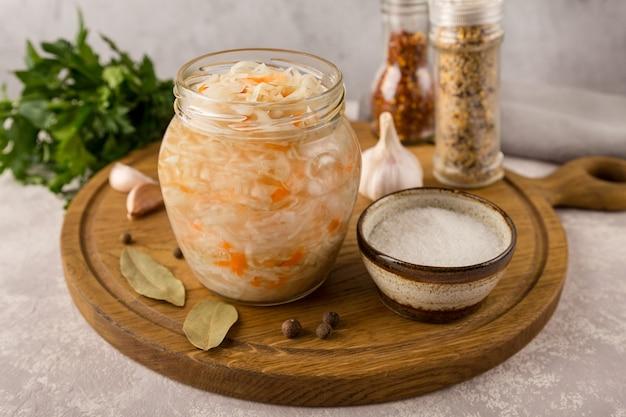 Aprire un barattolo di vetro di crauti fatti in casa sul tagliere rotondo da vicino con ingredienti su sfondo grigio