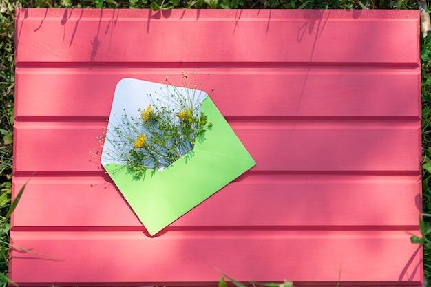 Busta verde aperta con fiori di campo su uno sfondo di legno rosa ciao dall'estate