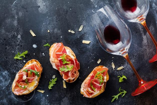 Panini aperti al prosciutto, rucola e formaggio a pasta dura, serviti su supporto in legno con un bicchiere di vino rosso su una vecchia superficie scura di cemento
