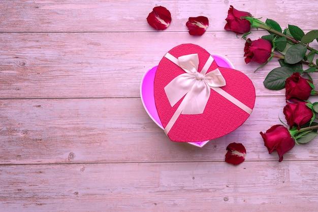 Regali per gli amanti della scatola a forma di cuore aperto su petali di rose di superficie in legno