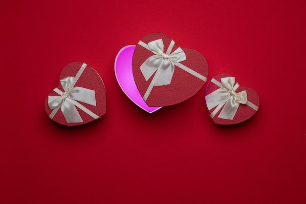 Scatole aperte a forma di cuore regali per amanti su superficie in feltro, rose, petali. san valentino 14 febbraio