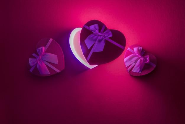 Scatole aperte a forma di cuore regali per amanti su superfici in feltro petali di rose