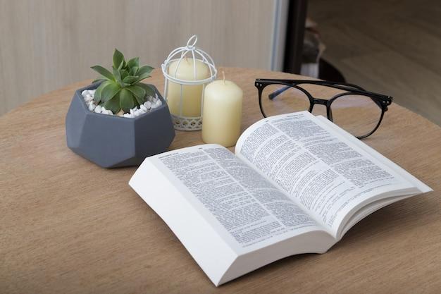 Aprire la sacra bibbia su una tavola rotonda con candele, piante e bicchieri