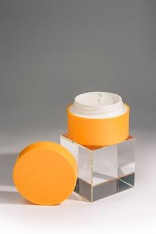 Un barattolo aperto di crema cosmetica e un cubo di vetro su una parete grigia e bianca con spazio di copia. cura della pelle del viso e del corpo.