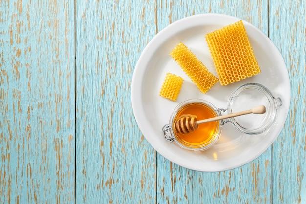 Aprire il vasetto di miele biologico sul tavolo rustico blu, vista dall'alto.