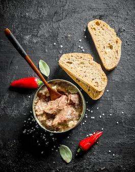 Barattolo aperto con carne in scatola con peperoncino e pane. sul nero rustico