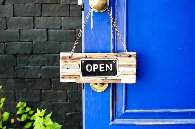 Etichetta aperta che appende sulla porta blu in giardino