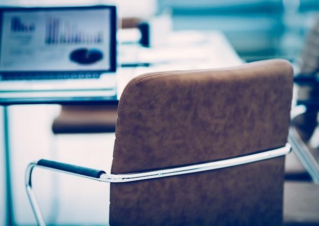 Computer portatile aperto con grafici finanziari sul tavolo con il manager in un ufficio moderno. la foto è uno spazio vuoto per il tuo testo
