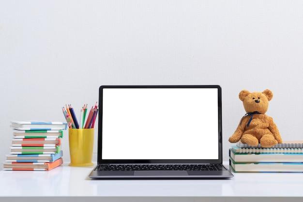 Apri il modello di laptop sul posto di lavoro dei bambini con libri e orsacchiotto. torna al concetto di apprendimento online della scuola