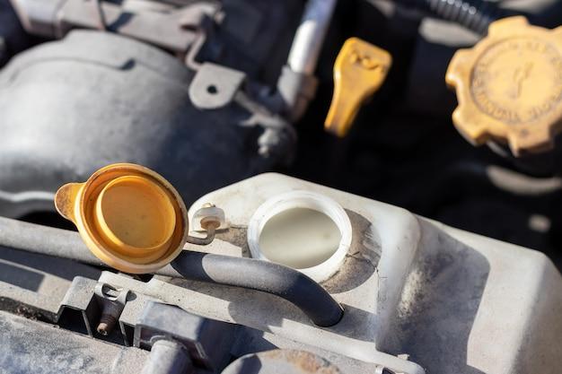 Aprire il coperchio sul serbatoio dell'antigelo dettagli polverosi del vano motore dell'auto boxer flatfour
