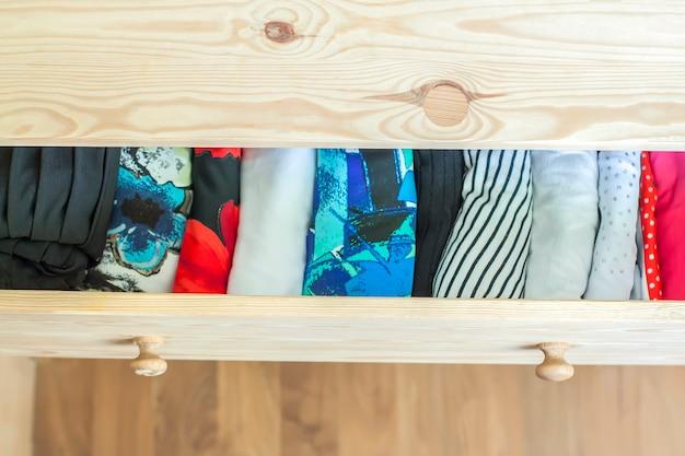Cassetto aperto in legno chiaro con vestiti colorati.