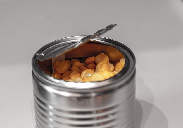Latta metallica aperta con mais dolce su un bianco.