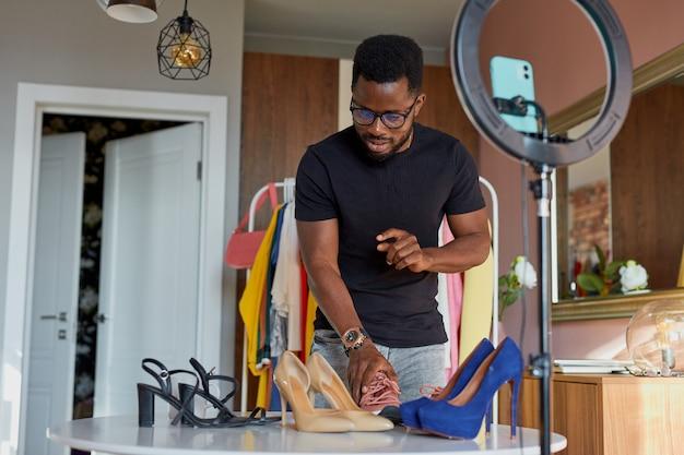 Blogger afro di mentalità aperta parla alla telecamera, mostra nuovi vestiti e scarpe